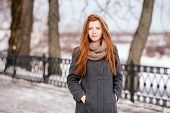 Lifestyle portrait of young beautiful redhead woman in coat and scarf walking in winter outdoors