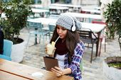Stylish hipster girl drinking fruit cocktail and use digital tablet in coffee shop poster