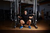 picture of squatting  - Strong young  athletic man in gloves preparing for exercises with barbell squats in the gym - JPG