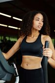 foto of cardio exercise  - Attractive young afro american girl with curly hair  exercising on a cardio machine in fitness center - JPG
