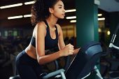 Side shot of attractive woman at the gym riding on the spinning bike with copy space