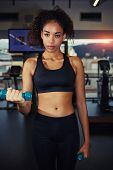 Portrait of attractive afro american woman lifting weights at the gym strong fit girl weightlifting