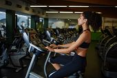 Side view picture of young woman with curly afro hair spinning on cardio simulator machine at gym