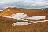July in Iceland. Smoldering underground heat hillsides. In the hollows are last year's snow fields