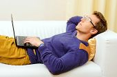 Goodlooking smiling young man lying on a couch at home and working on his laptop. Social networking.