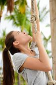 pic of toned  - Exercise cross fit woman doing body workout on climbing rope as toning exercises for arm toning - JPG