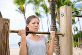 Fitness woman exercising on chin-up bar. Lady doing chin-ups training toned arms portrait outside on beach in summer.