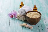 stock photo of salt-bowl  - Spa setting with sea salt soap towel and flower on aqua painted wooden boards - JPG