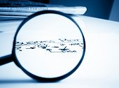 Business Plan Words See Through Lens Of Loupe In Front Of Business Newspaper On Office Table