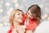 people, happiness, love, family and motherhood concept - happy mother and daughter hugging and talking over holiday lights background