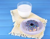 Glazed donut with glass of milk on napkin and color wooden background