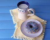 Glazed donut with cup of milk on napkin and color wooden planks background