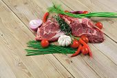 fresh raw meat : fresh red beef ribs with thyme , red chili pepper , cherry tomato , and garlic on wooden board