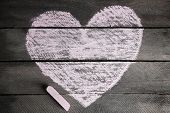 Heart drawn of chalk on wooden background close-up