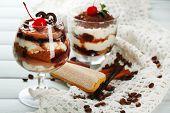 Tasty tiramisu dessert in glasses, on napkin, on wooden background