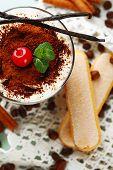 Tasty tiramisu dessert in glass, on napkin, on wooden background