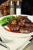 Steak with wine sauce on plate on wooden table