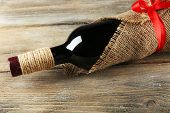 Red wine bottle wrapped in burlap cloth on wooden planks background