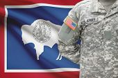 American Soldier With Us State Flag On Background - Wyoming