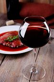 Glass of wine with grilled steak in wine sauce on wooden background