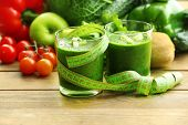 Green fresh healthy juice with fruits and vegetables on wooden table background
