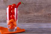Vegetables with chili pepper in glass on napkin and rustic wooden background