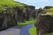 Iceland in the summer. Canyon Fjadrargljufur and cold fast river with a pebble bottom