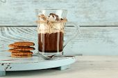 Cup of coffee with cream and cookies on wooden background