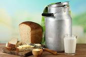 Retro can for milk with fresh bread and glass of milk on wooden table, on bright background. Bio products concept