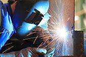 welder is welding chekered plate with all safety