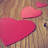 some red hearts of different sizes on a rustic wooden surface, with a filter effect