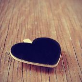 a blank heart-shaped chalkboard with a copy space on a rustic wooden surface, with a filter effect