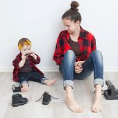 Mother And Baby In Red Checkered Shirts And Jeans