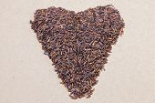 Heart shape brown rice on wooden background