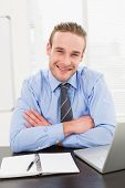 Smiling businessman with arms crossed at his desk in the office