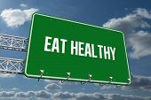 The word eat healthy and green billboard sign against sky and clouds