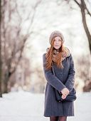 Winter portrait of a cute redhead lady in grey coat and scarf in the park