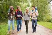 adventure, travel, tourism, hike and people concept - group of smiling friends with backpacks and map walking outdoors