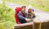 adventure, travel, tourism, hike and people concept - smiling couple with backpacks standing at signpost outdoors