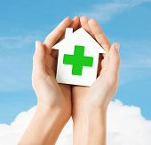 care, help, charity and people concept - close up of hands holding white paper house with green cross sign over blue sky and cloud background
