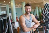 Athletic man standing by treadmill in gym