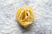 raw pasta and flour on table