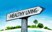 Healthy Living sign with a beach on background