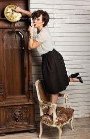 image of pendulum  - Beautiful Woman Rewinding A Vintage Clock With Pendulum - JPG