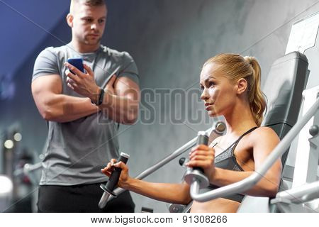 sport, fitness, bodybuilding, teamwork and people concept - young woman and personal trainer flexing