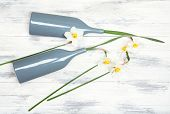 foto of daffodils  - Beautiful daffodils in vases on wooden background - JPG