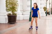 pic of inline skating  - Cute young Hispanic woman having fun and skating in the city  - JPG