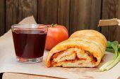 pic of scallion  - Pizza stromboli cut with glass of red wine fresh scallion and tomato copyspace horizontal - JPG
