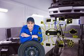 pic of auto repair shop  - Handsome mechanic leaning on tire against auto repair shop - JPG