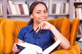 picture of toothless smile  - Beautiful African female student holding a book and smiling while sitting at the chair in library - JPG